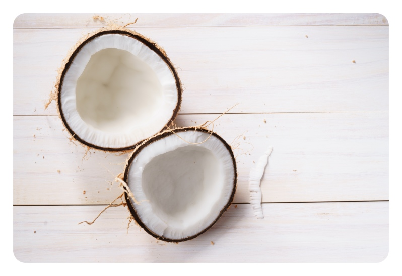 coconut with shell on white wooden background